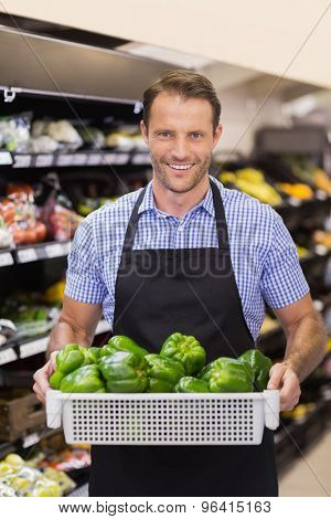 Portrait of a smiling handsome worker holding a box with vegetables in supermarket