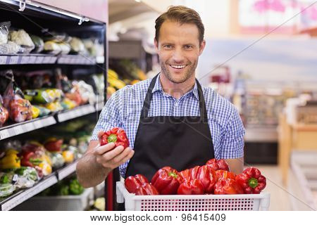 Portrait of a smiling handsome taking a vegetable on his hand in supermarket