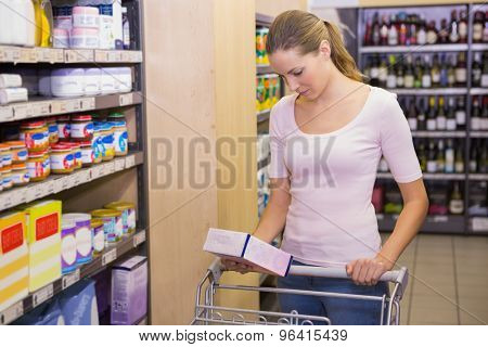 Pretty woman picking box in shelf in supermarket