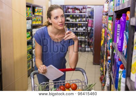 Pretty woman looking at product on shelf and holding grocery list at supermarket