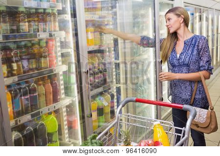 a woman taking a bottle in the frozen aisle at supermarket