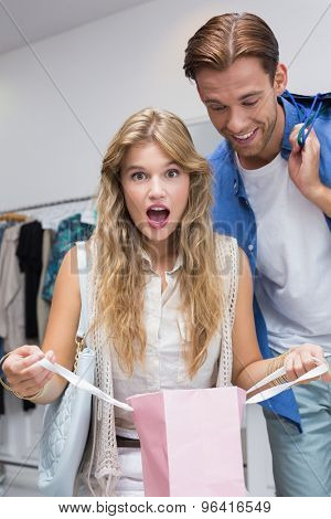 A surprised couple with shopping bags at the clothing