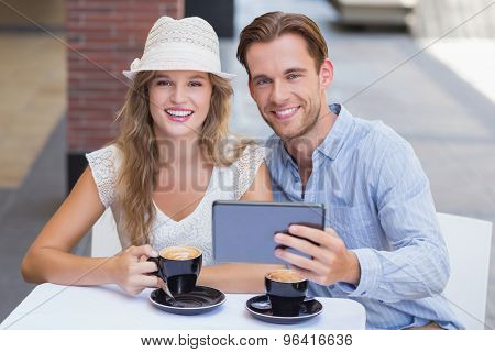 Portrait of a smiling cute couple holding a tablet