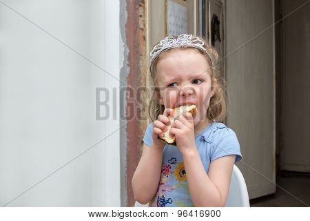 Little Girl In Diadem Hungrily Bites Sandwich