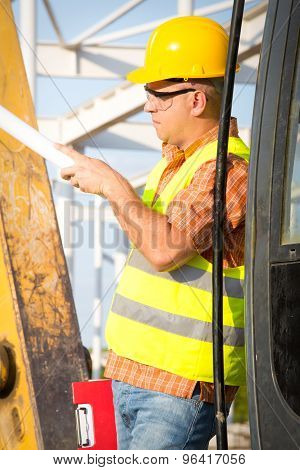 Construction manager controlling building site with plan on construction site