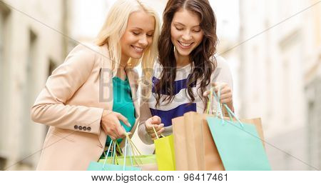 sale, shopping, tourism and happy people concept - two beautiful women looking inside shopping bags