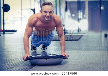 Portrait of a muscular man doing bosu ball exercises