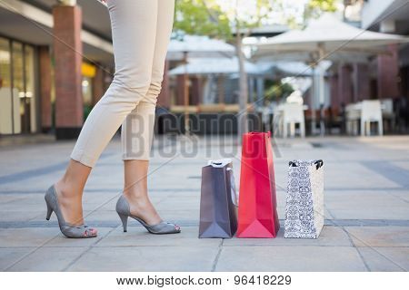 Woman standing next to her shopping bags at the mall