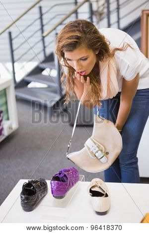 Astonished woman looking at laced shoes at a shoe shop
