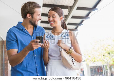Young happy couple looking at mobile phone before shopping