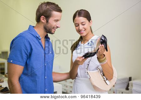 Young happy couple looking at shoes in the shoe store