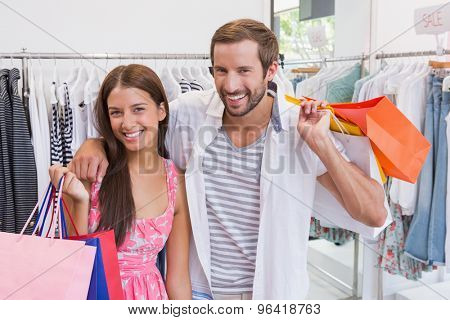 Portrait of smiling couple with shopping bags at a boutique