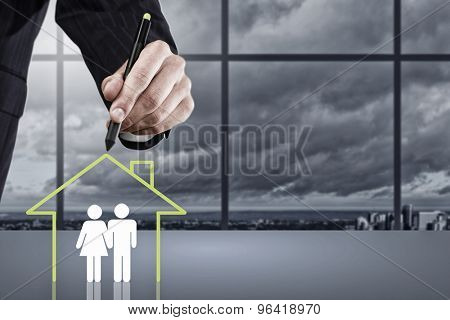 Close up of human hand drawing happy family and real estate concept