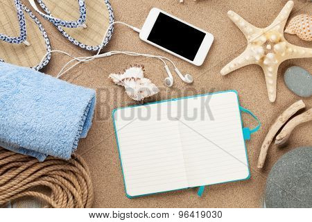 Smartphone and notepad on sea sand with starfish and shells. Top view with copy space