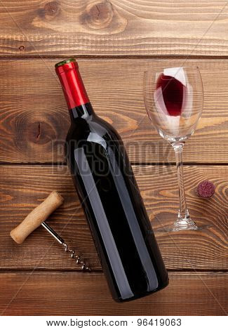 Red wine bottle, glass and corkscrew on wooden table background. Top view