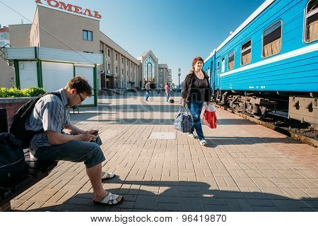 Unidentified people waiting on train on the station platform
