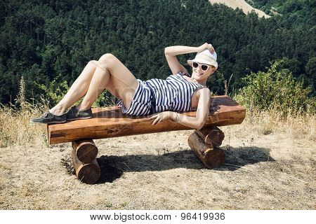 Young Woman With Hat Posing In Sailor Outfit On A Wooden Bench