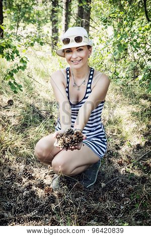Smiling Woman Enjoying The Pine Cones In The Forest By Summer