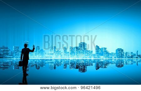 Businessman standing with back against night city panoramic view