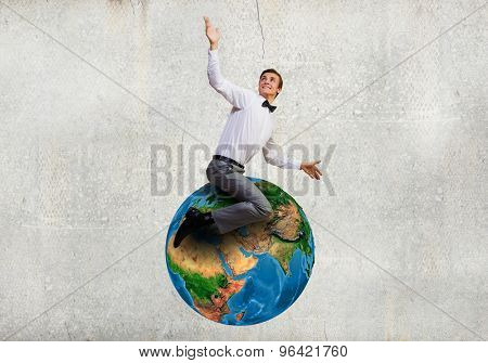 Young businessman riding Earth planet. Elements of this image are furnished by NASA