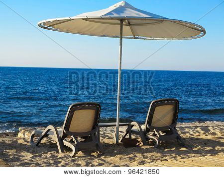 Two Deckchairs And Umbrella On Blue Sea Sand Beach