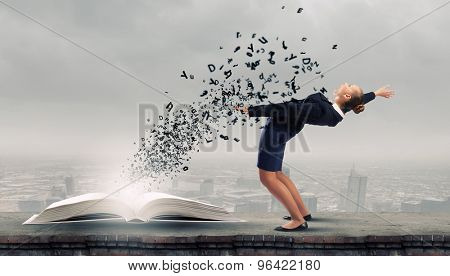 Young woman benting to evade characters flying from book