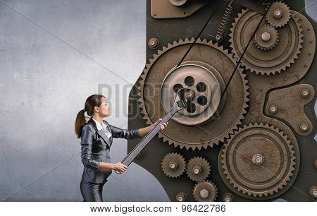 Young businesswoman fixing gears mechanism with wrench