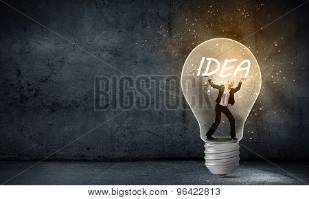 Businesswoman holding luminous idea inside light bulb