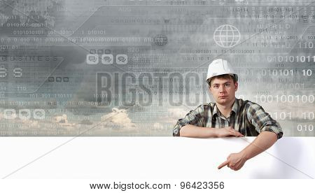 Young builder man with white blank banner. Place for text