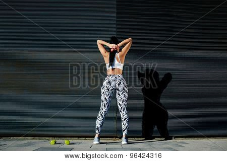 Portrait sporty woman with perfect figure and buttocks stretching her arms against wall