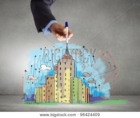Close up of businessman hand drawing sketches of buildings