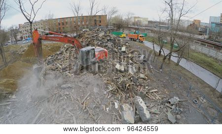 MOSCOW - APR 17, 2015: Excavator moves old building remains at spring cloudy day. Aerial view