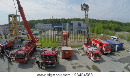 MOSCOW - MAY 29, 2015: Group of people lift in cabin of fire-engine at spring sunny day. Aerial view