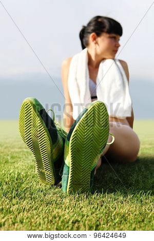 green sole of shoes on grass, tired sportswoman