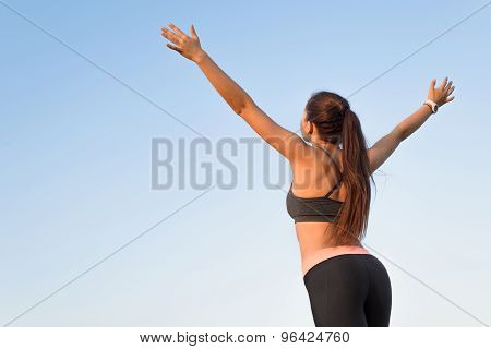 Woman is back raising arms to the sky.