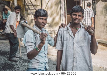 MUMBAI, INDIA - 08 JANUARY 2015: Two young Indian workers stand in street with hoe's in hands. Post-processed with grain, texture and colour effect.