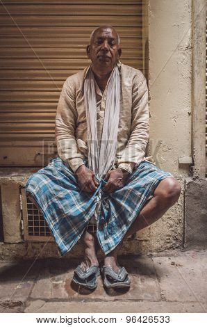 VARANASI, INDIA - 20 FEBRUARY 2015: Indian man sitting next to closed store wearing shirt, scarf,lungi and slippers. Post-processed with grain, texture and colour effect.