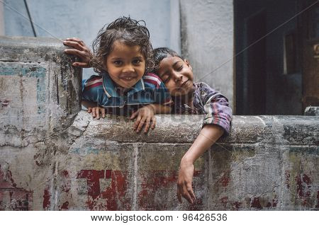 VARANASI, INDIA - 20 FEBRUARY 2015: Two siblings enjoy each others company. Brother resting on sisters sholder. Post-processed with grain, texture and colour effect.