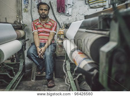 VARANASI, INDIA - 21 FEBRUARY 2015: Worker sits on chair next to textile machine in small factory. Post-processed with grain, texture and colour effect.