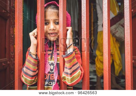 VARANASI, INDIA - 20 FEBRUARY 2015: Little girl with runny nose looks through closed fence of a small temple. Post-processed with grain, texture and colour effect.