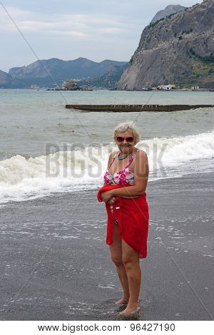Aged Woman On Surf Waves And Cliff Background, Crimea, Russia.