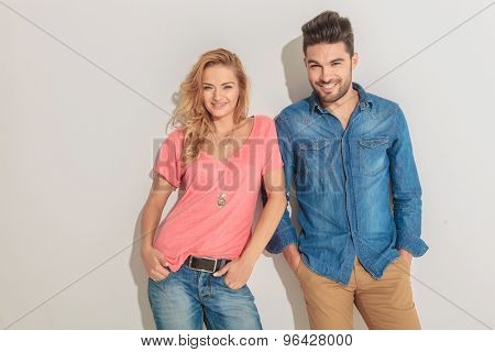 Young happy couple leaning on a wall, both holding hands in pockets.