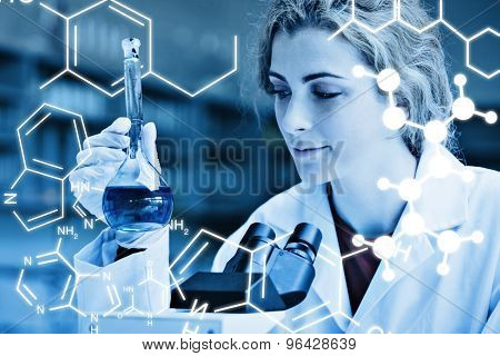 Science graphic against smiling student looking at a blue liquid
