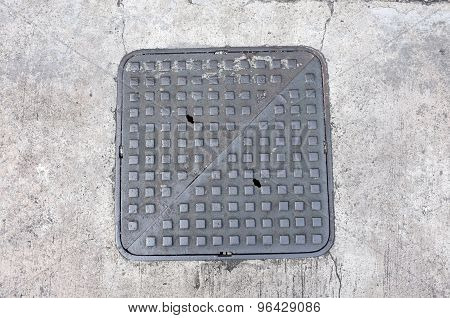 Metal hatch sewer manhole on pavement
