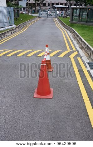 Red cones and yellow striped warning road