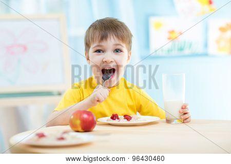 cheerful kid eating healthy food at home or kindergarten