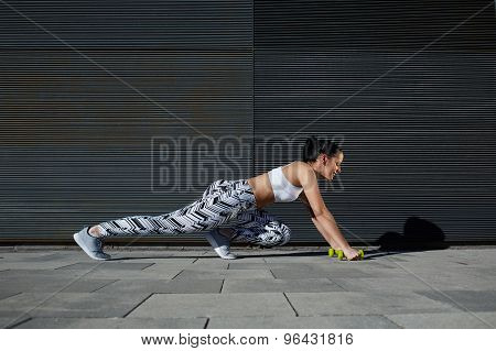Woman with perfect figure and buttocks shape stretch legs with dumbbells near copy space wall