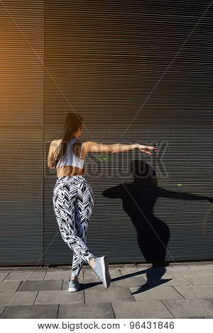 Sporty woman with perfect figure and buttocks shape exercising against wall with copy space