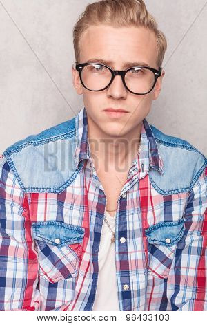 portrait of a handsome blond man in casual clothes and gasses looking at the camera