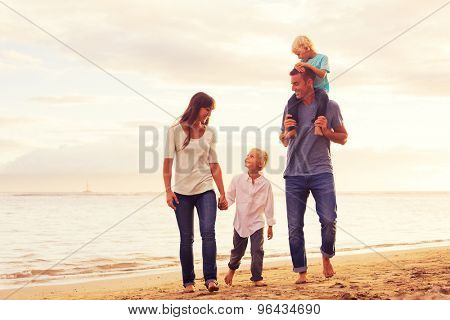Happy young family having fun walking on the beach at sunset